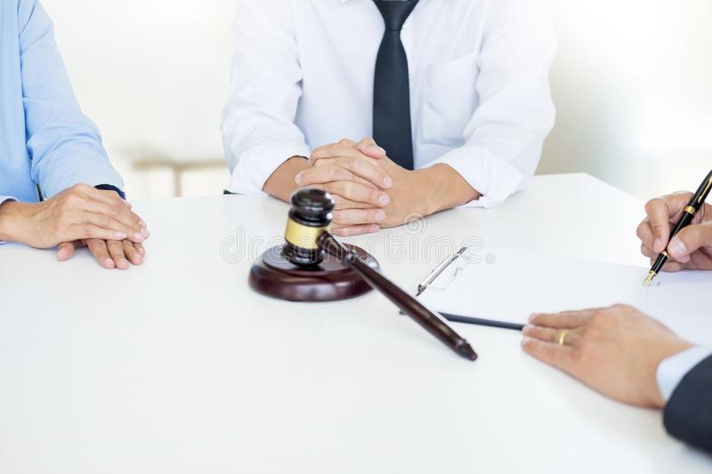 Angry couple arguing telling their problems to Judge gavel deciding on marriage to conclude an agreement on the divorce. They qua. Rrel and argue with each other stock photo