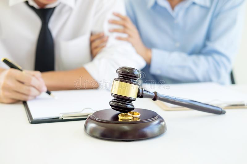 Angry couple arguing telling their problems to Judge gavel deciding on marriage to conclude an agreement on the divorce. They qua. Rrel and argue with each other stock photography
