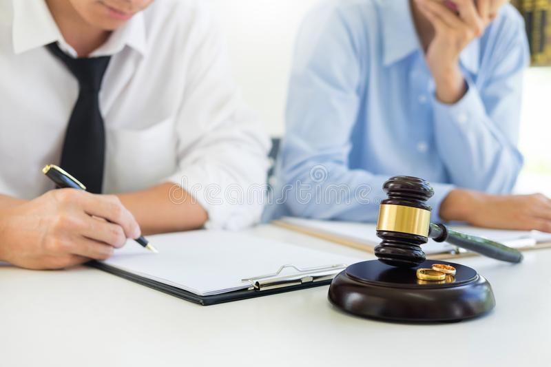 Angry couple arguing telling their problems to Judge gavel deciding on marriage to conclude an agreement on the divorce. They qua. Rrel and argue with each other stock images