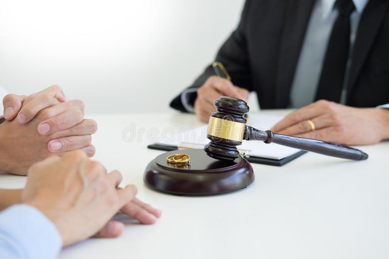 Angry couple arguing telling their problems to Judge gavel deciding on marriage to conclude an agreement on the divorce. They qua. Rrel and argue with each other royalty free stock photo