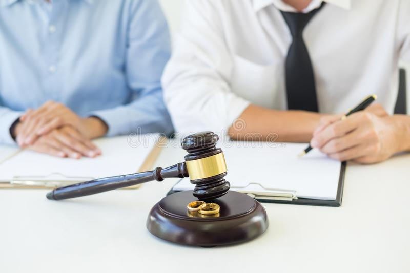 Angry couple arguing telling their problems to Judge gavel deciding on marriage to conclude an agreement on the divorce. They qua. Rrel and argue with each other royalty free stock image