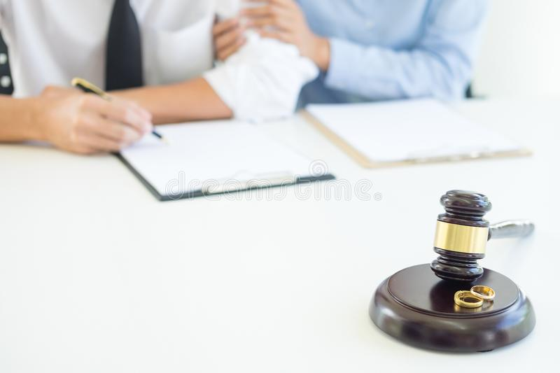 Angry couple arguing telling their problems to Judge gavel deciding on marriage to conclude an agreement on the divorce. They qua. Rrel and argue with each other stock photos