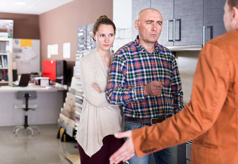 Angry couple customers at kitchen store. Angry couple customers at kitchen furniture store royalty free stock photos