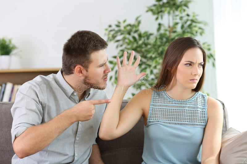 Angry couple fighting on a couch at home. Angry couple fighting sitting on a couch at home royalty free stock image