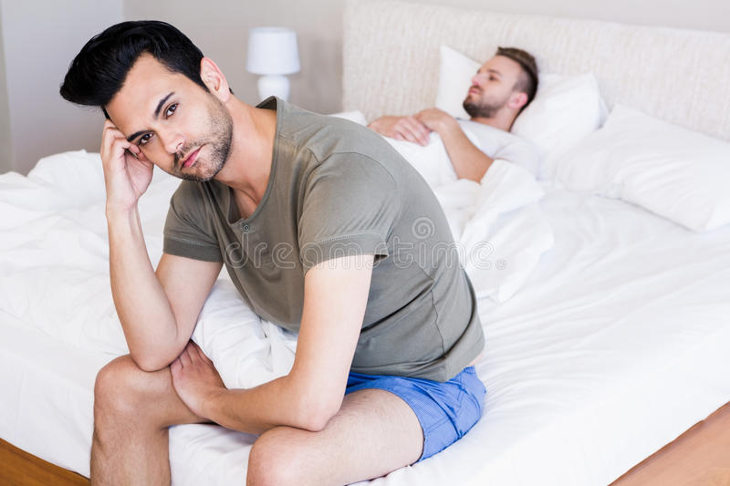 Angry couple gay in bedroom stock photography