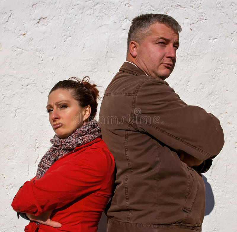 Angry couple. Angry men (red in the face - off) leaning with angry and serious expression in their faces standing back on back. Vertical color photo royalty free stock image