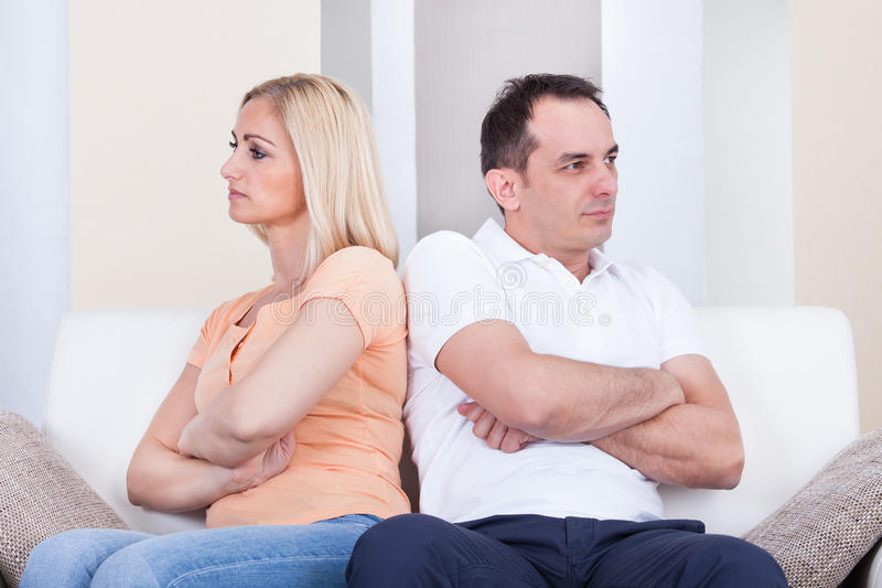 Angry couple sitting on sofa. Portrait of mid-adult couple sitting on sofa after quarrel stock photo