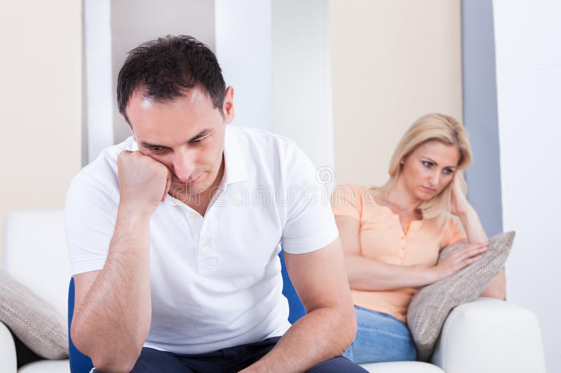 Angry couple sitting on sofa. Portrait of mid-adult couple sitting on sofa after quarrel royalty free stock image