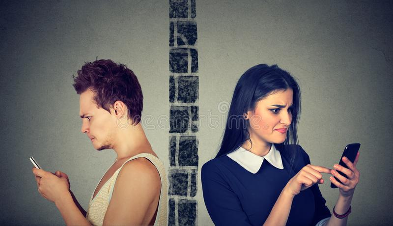 Angry couple upset man and woman separated by wall tasting each other on mobile phone stock images