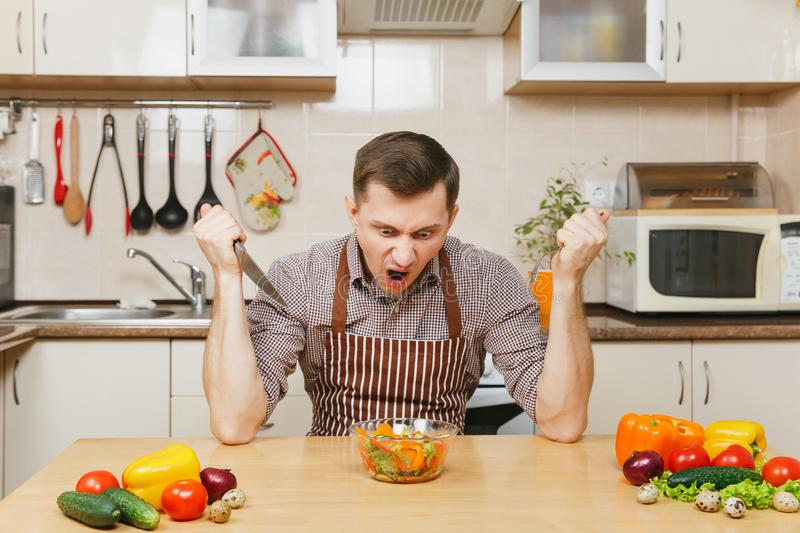 Handsome caucasian young man, sitting at table. Healthy lifestyle. Cooking at home. Prepare food. stock photo