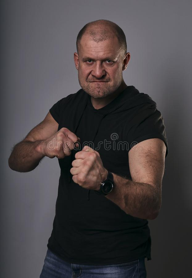 Angry crime man with bald head going to fight showing the fists in black shirt on dark grey background. Closeup royalty free stock image