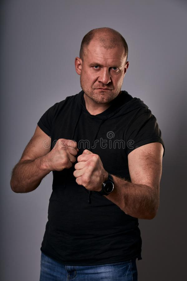 Angry crime man with bald head going to fight showing the fists in black shirt on dark grey background. Closeup stock images