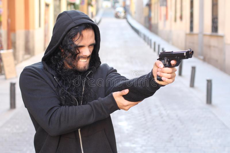 Angry criminal holding a gun outdoors stock photography