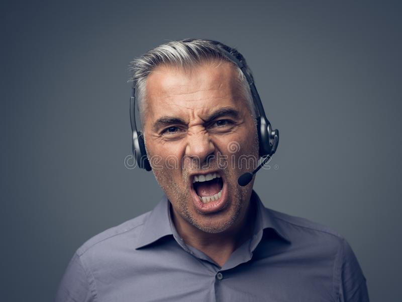 Angry customer support phone operator. Angry aggressive customer support phone operator with headset, he is yelling and having a dicussion with a customer stock photos