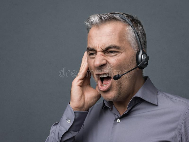 Angry customer support phone operator. Angry aggressive customer support phone operator with headset, he is yelling and having a dicussion with a customer stock photography