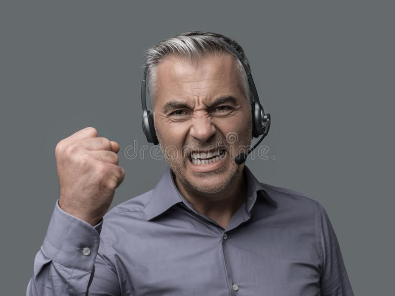 Angry customer support phone operator. Angry aggressive customer support phone operator with headset, he is yelling and having a dicussion with a customer royalty free stock photography