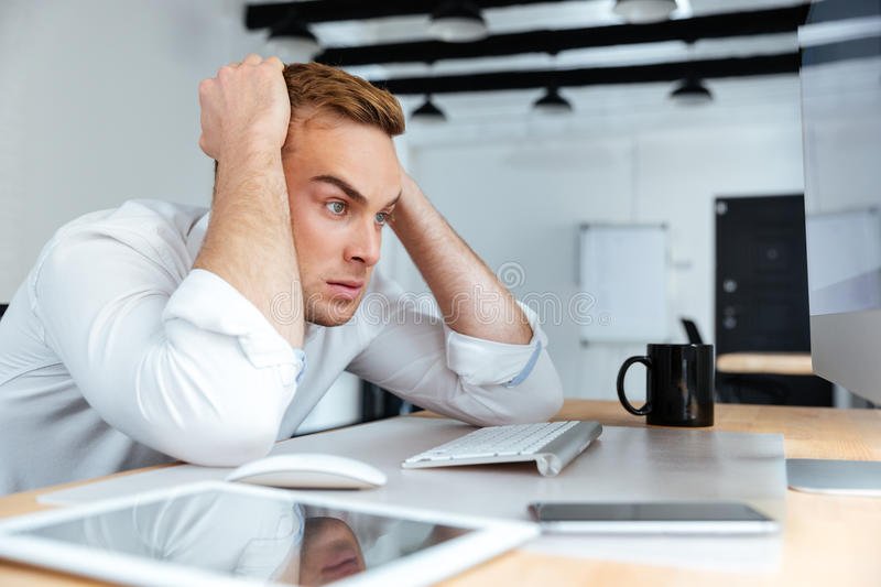 Angry desperate young businessman sitting at the table stock photos