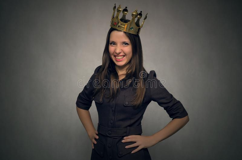 Selfish arrogant woman. Angry and disgruntled woman boss with golden crown above her head. Angry and smug client concept stock image