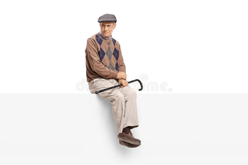 Angry elderly man sitting on a panel stock photos