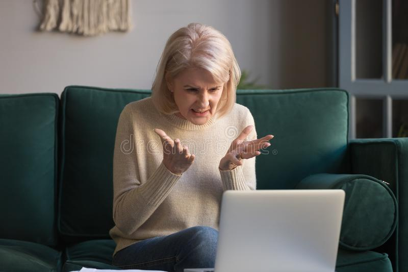 Frustrated mature woman get mad having problems on laptop royalty free stock photography