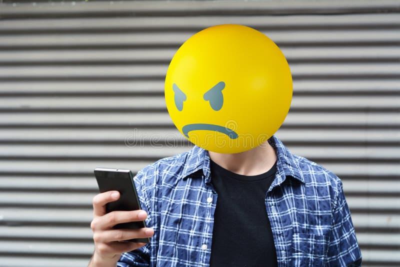 Angry emoji head man. Using a smartphone stock photos