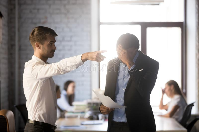 Angry executive manager dismiss incompetent African American employee, royalty free stock photo