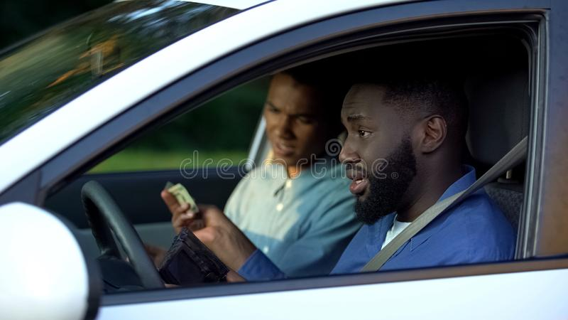 Angry father giving pocket money to son sitting in auto, parenthood conflict stock images