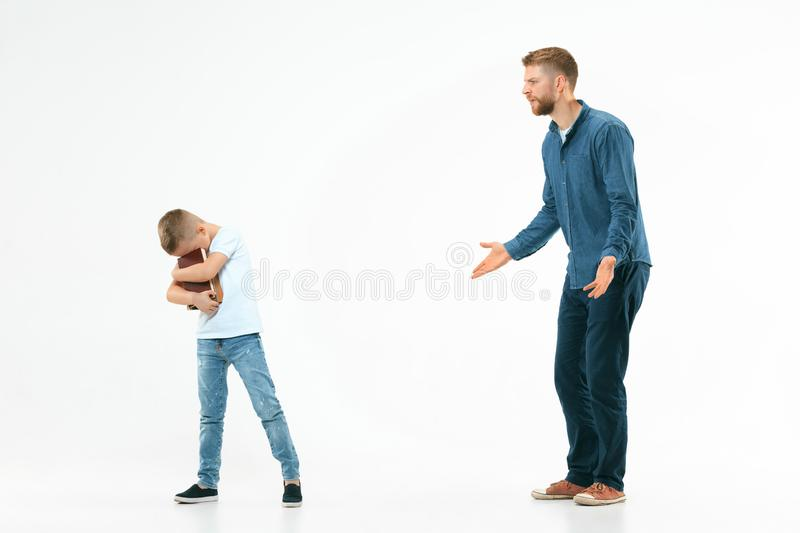 Angry father scolding his son in living room at home royalty free stock image