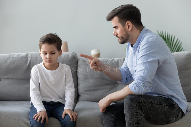 Angry father scolding sad kid son for bad behavior. Angry mad father scolding lecturing sad preschool kid son for bad behavior at home, serious parent dad punish stock images