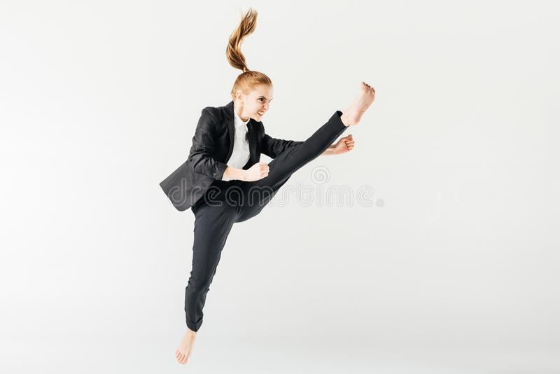angry female karate fighter jumping and performing kick in suit royalty free stock image