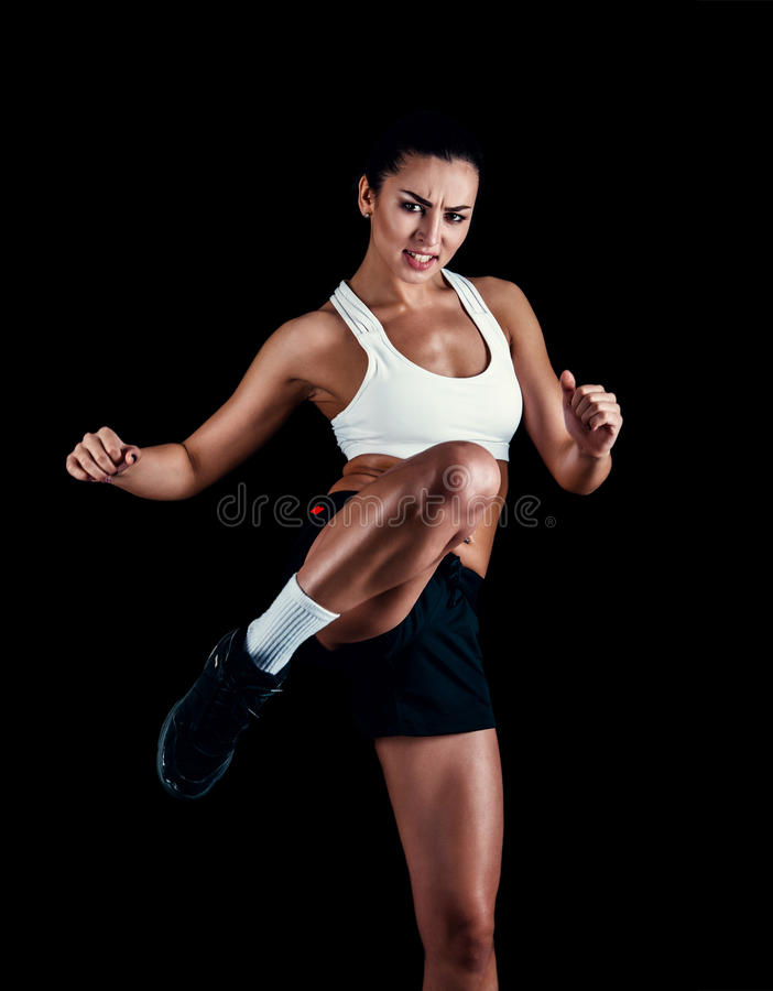 Angry fitness girl ready for fight on black background. royalty free stock image