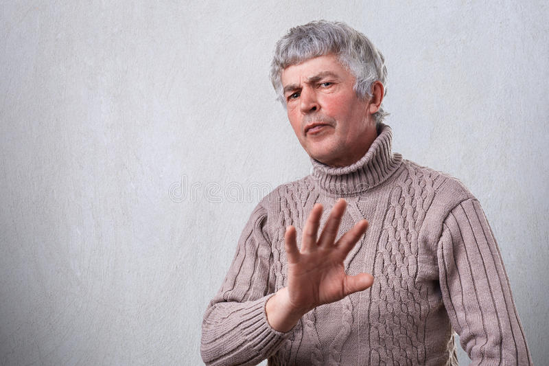 An angry frowning mature man having negative expression showing refusing sign with palm. Negative human emotion face expression fe royalty free stock photo