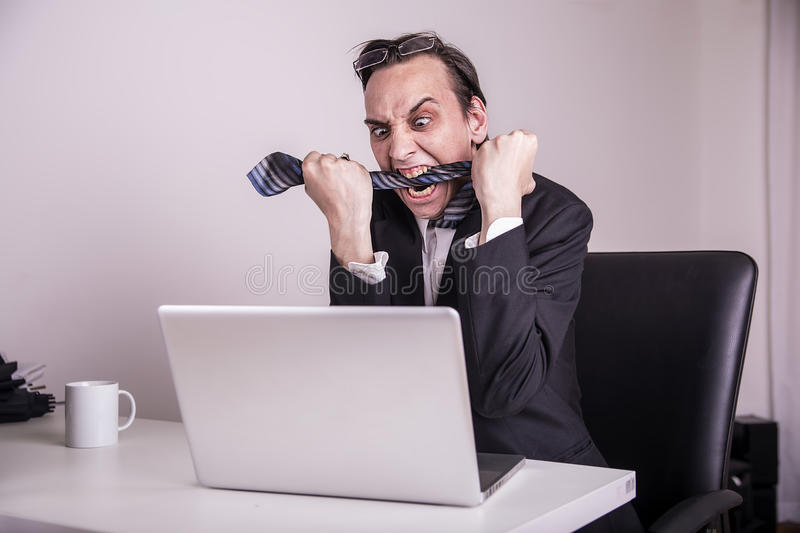 Angry and frustraded business man eating his tie in the office. Angry business man eating his tie in the office royalty free stock image
