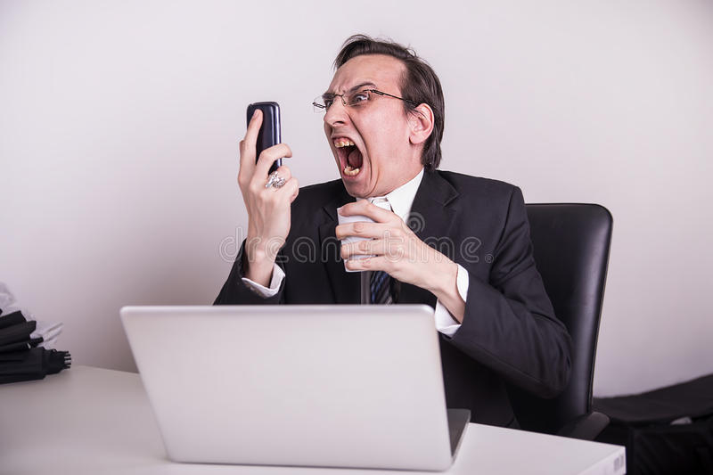 Angry and frustraded business man screaming on a cell phone in the office. Angry business man screaming on a cell phone in the office royalty free stock images