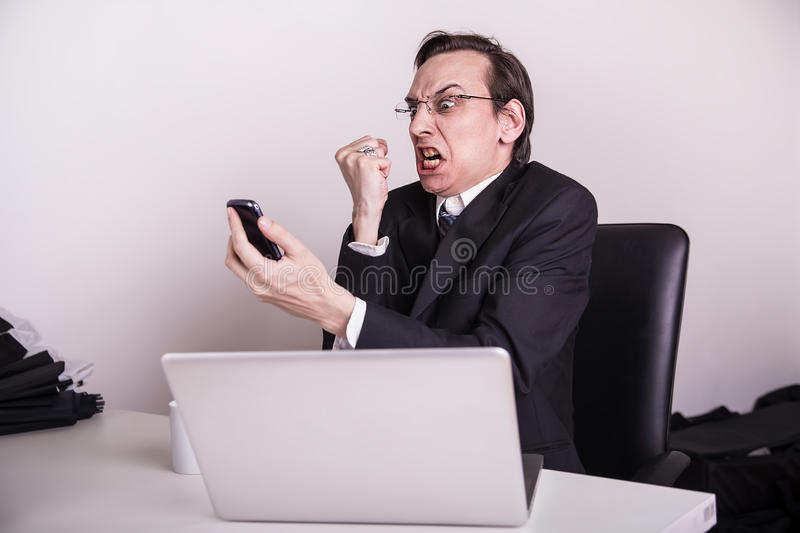 Angry and frustraded business man screaming on a cell phone in the office. Angry business man screaming on a cell phone in the office royalty free stock image