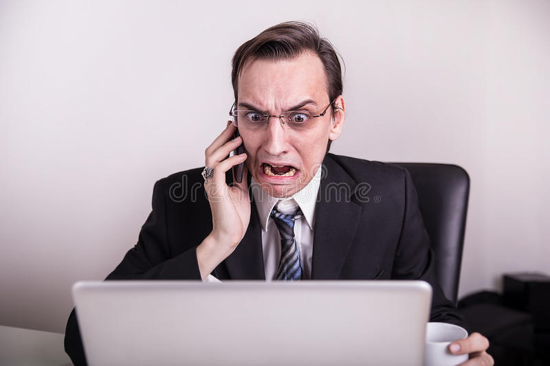 Angry and frustraded business man talking on a cell phone and screaming on his laptop in the office. Angry business man talking on a cell phone and screaming on royalty free stock photo