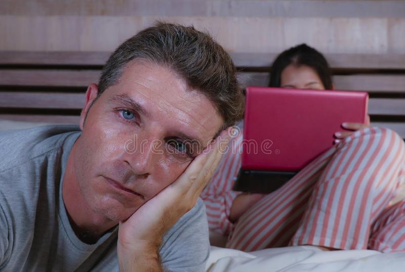 Angry and frustrated husband moody in bed ignored by his workaholic wife or internet social media addict girlfriend using laptop. In bed ignoring the men in stock photography
