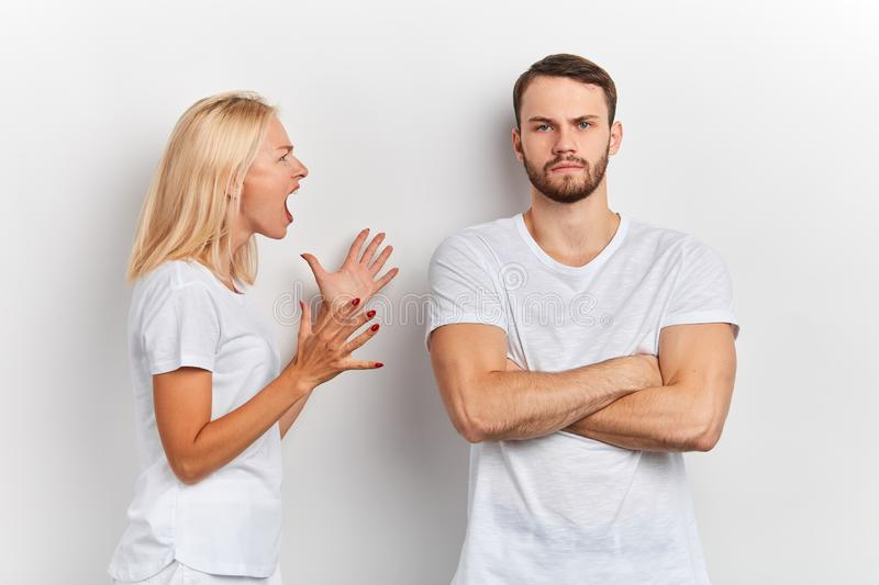 Angry frustrated women shouting at man who standing with crossed arms stock images