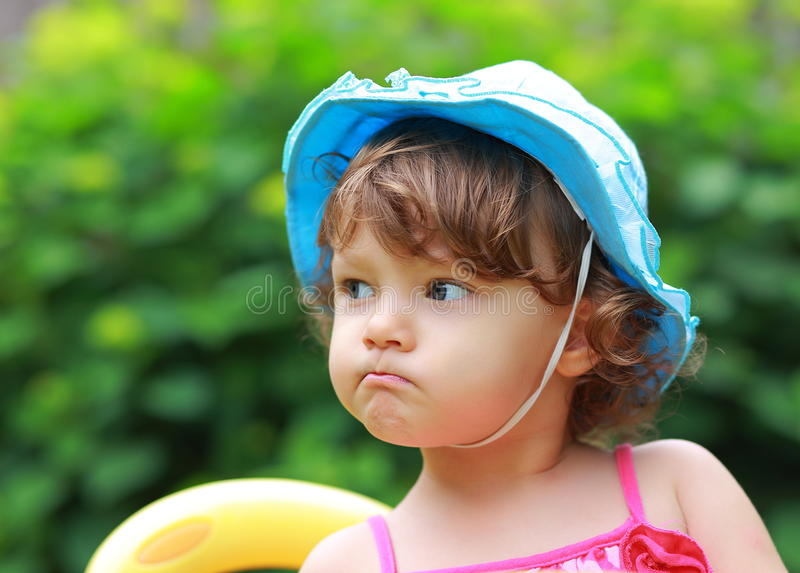 Angry fun girl looking in blue hat stock photography