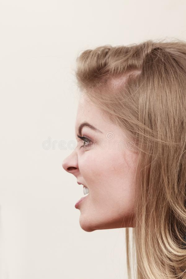 Angry furious woman screaming, profile view. Angry furious blonde woman screaming and yelling at somebody, profile view. Yellow background royalty free stock images