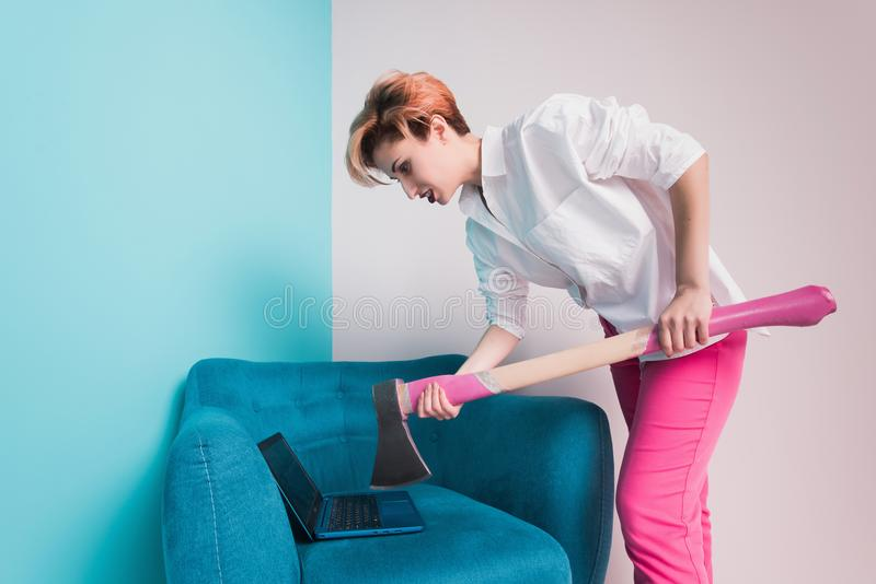 Angry furious businesswoman girl with an ax smashes a laptop, screaming. Negative human emotions, facial expressions, feelings, ag. Gression, anger management royalty free stock photography