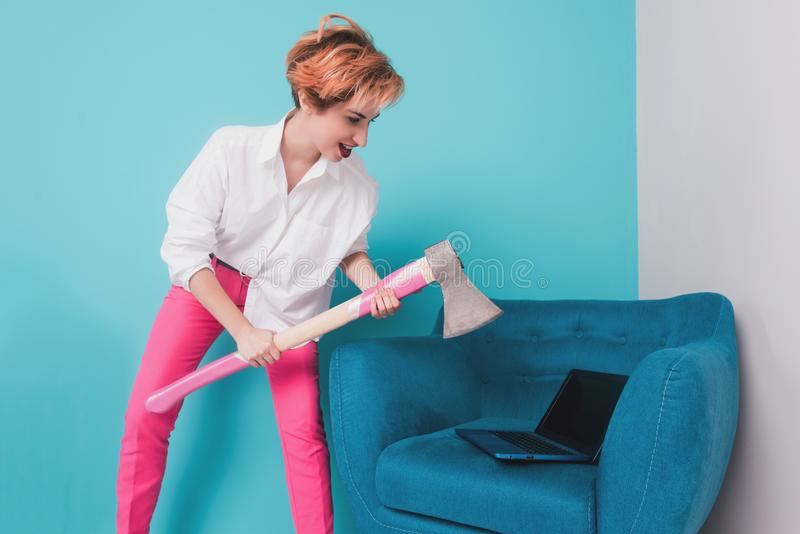 Angry furious businesswoman girl with an ax smashes a laptop, screaming. Negative human emotions, facial expressions, feelings, ag. Gression, anger management stock photos