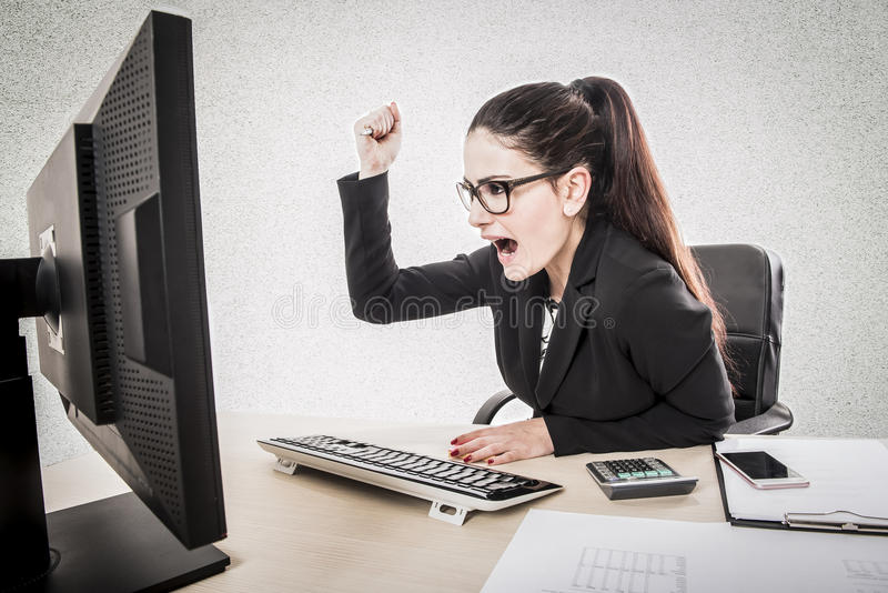 Angry furious businesswoman working on computer. stock photo