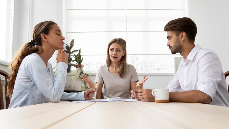 Angry furious female boss scolding employees for bad work stock images