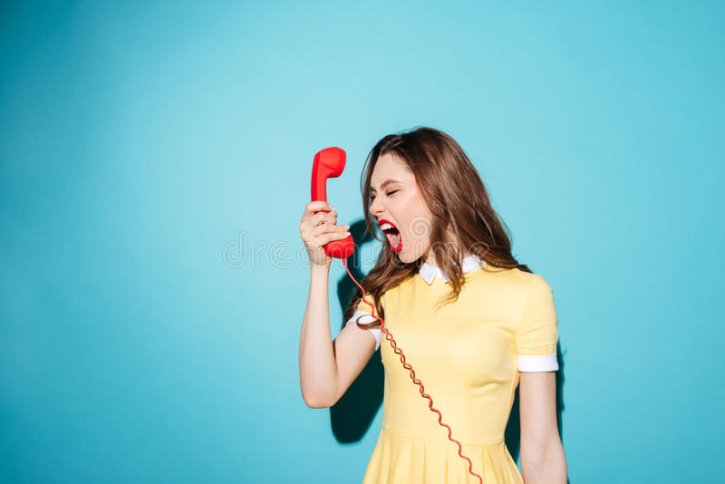 Angry furious girl in dress screaming at retro telephone tube royalty free stock photos