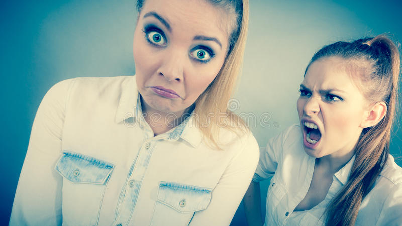 Angry fury girl screaming at her friend or younger sister. Conflict, bad relationships, friendship difficulties. Two young women having argument. Angry fury girl stock photo