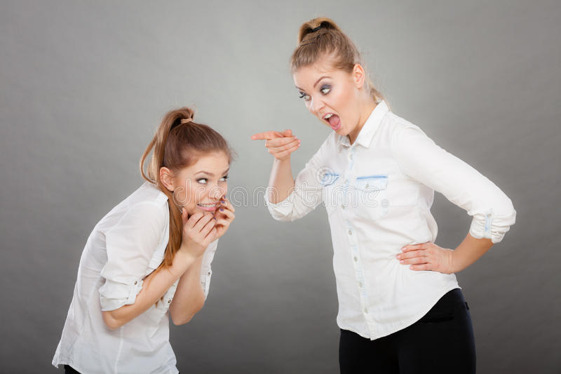 Angry fury girl screaming at her friend or younger sister. Conflict, bad relationships, friendship difficulties. Two young women having argument. Angry fury girl stock images