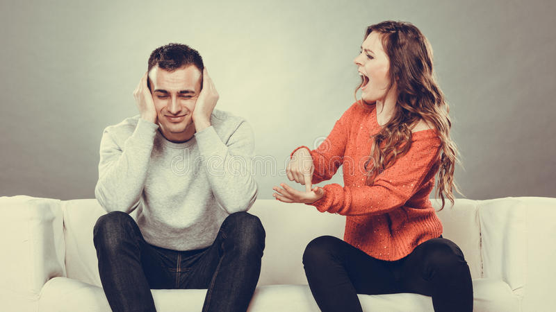 Angry fury woman screaming man closes his ears. Couple having argument - conflict, bad relationships. Angry fury women screaming men closing his ears royalty free stock photos