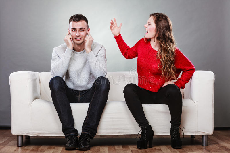 Angry fury woman screaming man closes his ears. Couple having argument - conflict, bad relationships. Angry fury women screaming men closing his ears royalty free stock image