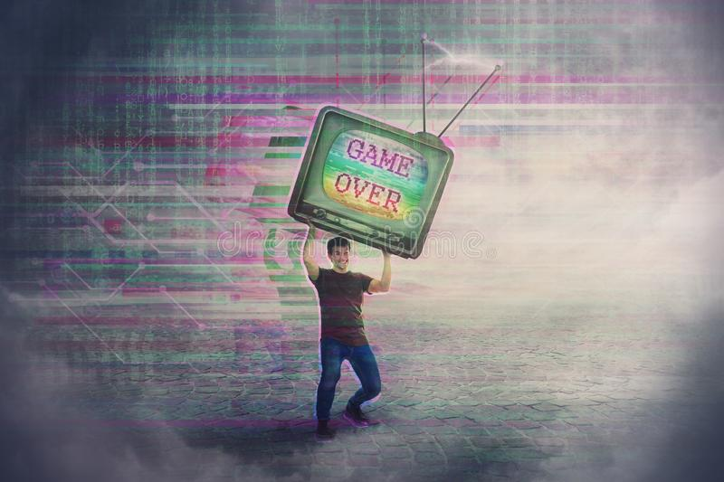 Angry gamer lifting up and throwing his old TV box after glitch text game over on the screen. Addicted, guy playing video games, stock photos